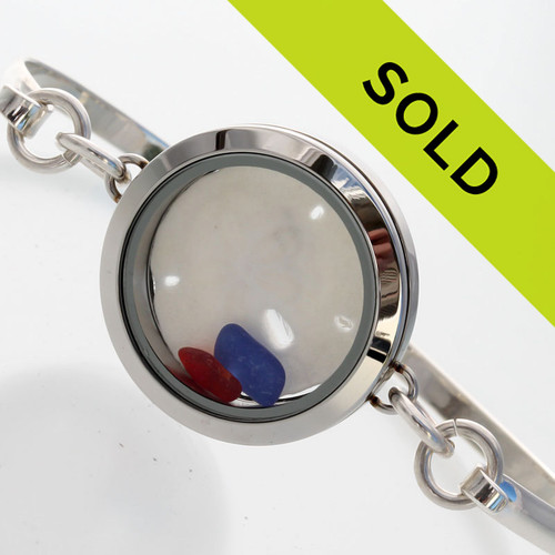 Tiny beach found red and blue sea glass combined with beach sand and a large sandollar in a stainless steel locket.