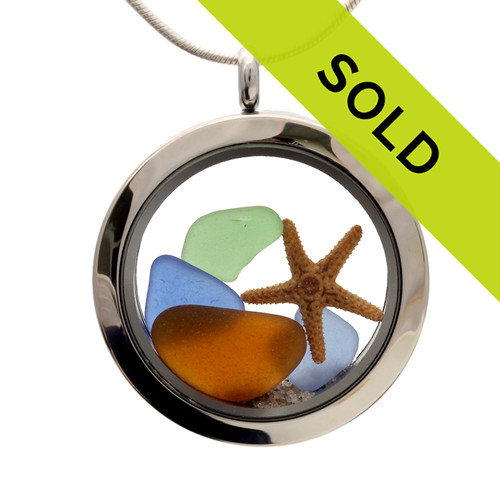 Sea glass in jeweltone colors of green, amber and blues combined with a real starfish and beach sand in this one of a kind stainless steel locket necklace.  Sorry this piece has SOLD!