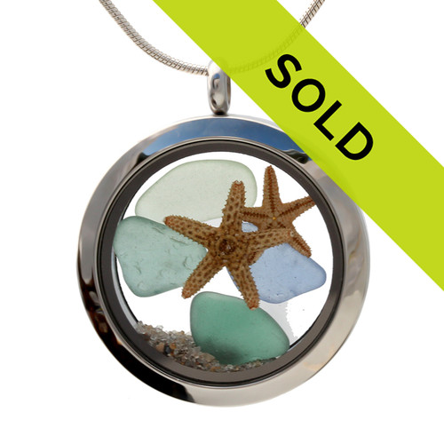 Pastel sea glass in greens, aqua and light blue are combined with two starfish for a beautiful sea glass locket necklace.