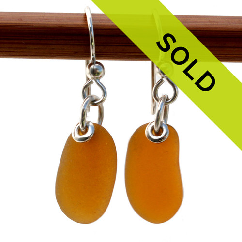 Vivid bright amber brown sea glass earrings in a simple silver setting.