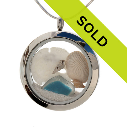 A beautiful and rare piece of flashed aqua and white sea glass combined with shells, and a real sandollar in this one of a kind sea glass locket necklace.