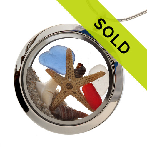 Red , white and blue sea glass are combined with a real baby starfish, baby shells and white sharks tooth in this stainless steel locket necklace.  SORRY THIS PIECE HAS SOLD!