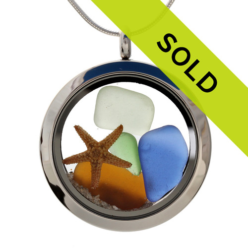 Sea glass in jeweltone colors of green, amber and blues combined with a real starfish and beach sand in this one of a kind stainless steel locket necklace.