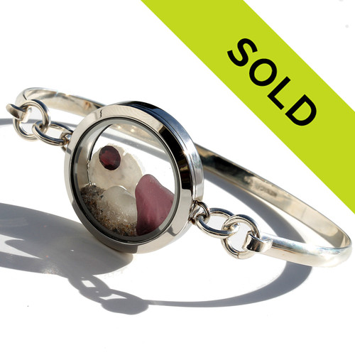 A piece of pattern plum sea glass and the palest purple sea glass combined with amethyst gems and a real sandollar in this one of a kind sea glass bangle bracelet.