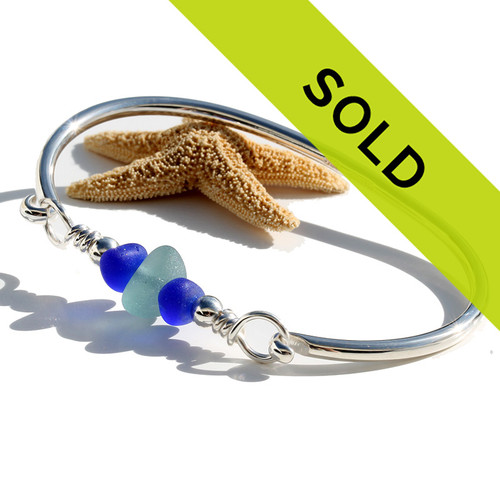 Genuine aqua blue sea glass is combined with cobalt blue frosted glass beads on our solid sterling round bangle bracelet.