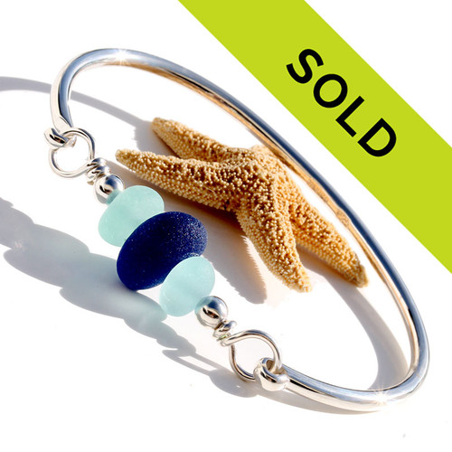 Thick and almost perfectly round deep blue and vivid aqua blue sea glass pieces set on our best solid sterling silver bangle bracelet.!