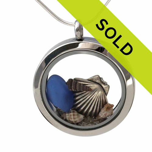 Simple small blue sea glass combined with a  sterling silver shell with small real beach shells in this beach on the go stainless steel locket necklace.