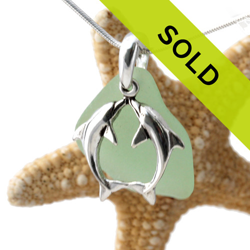 A perfect piece of natural yellowy seafoam green sea glass set on a solid sterling hand cast bail with a sterling silver kissing dolphins charm. A perfect sea glass necklace for any sea glass lover!