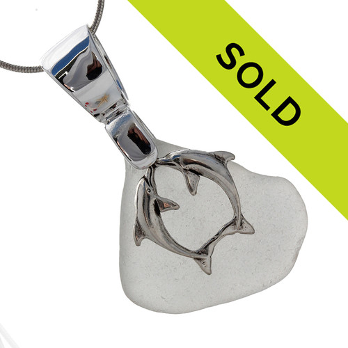 A large piece of pure white sea glass set on a solid sterling hand cast bail with a sterling silver kissing dolphins charm. A perfect sea glass necklace for any sea glass lover!