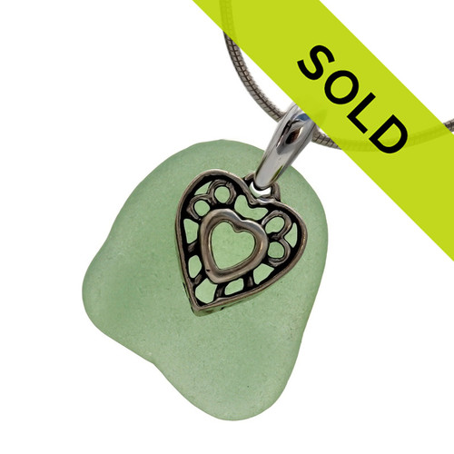 A large piece of natural vivid seafoam green sea glass set on a solid sterling hand cast bail with a sterling silver heart in hearts charm. A perfect sea glass necklace for any sea glass lover!