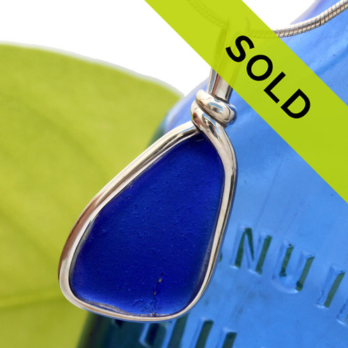 A blue sea glass necklace pendant in our Original Wire Bezel setting. A nicely shaped piece of beach found sea glass in a rare color.