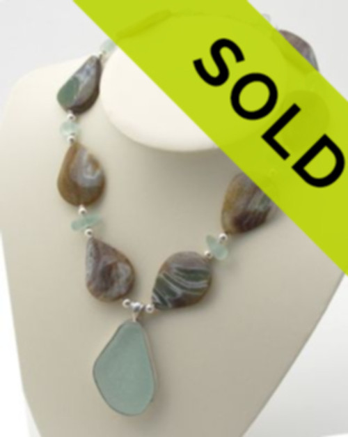 An amazing piece of round aqua sea glass in our Deluxe Wire Bezel setting combine with HUGE tumbled vintage Agate beads and recycled aqua glass spacer beads.  Sterling beads and clasp finish the piece for an elegant professional look.  Great earthy colors for any season! The necklace measures 20+ inches and the pendant is a 2 3/4 long by 1 1/2 inches wide and 1/4 inch thick. The sea glass center piece mimics the teardrop shape of the agates.  Comes with a deluxe presentation box perfect for gift giving!