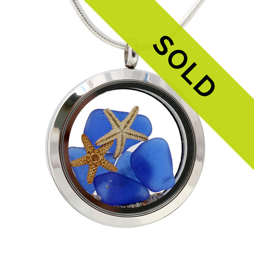 Blue sea glass pieces combined with a a pair of real starfish and beach sand in this sea glass locket necklace.
