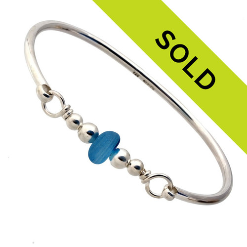 A perfect piece of vivid mixed blue sea glass combined with sterling beads and a small bangle bracelet. The sea glass is beach found and tumbled only by tide and time found on the beaches of Seaham England.