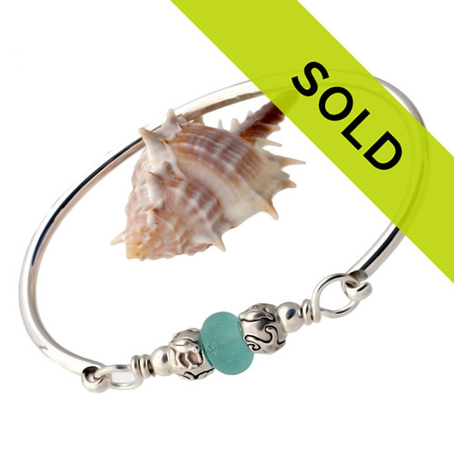 A perfect piece of vivid aqua blue sea glass combined with sterling sea life beads and a large bangle bracelet. The sea glass is beach found and tumbled only by tide and time found on the beaches of Seaham England.