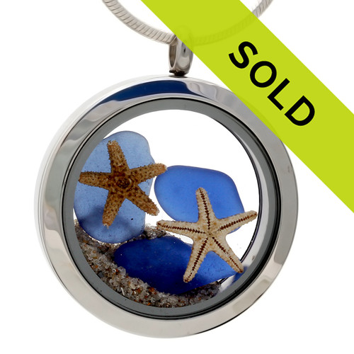 Blue sea glass pieces combined with a real starfish and beach sand in this sea glass locket necklace.