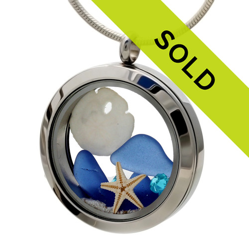 Blue sea glass pieces combined with a real starfish, sandollar and a mini aqua shell in this sea glass locket necklace. Aquamarine gems make this a great gift for a March Birthday.
