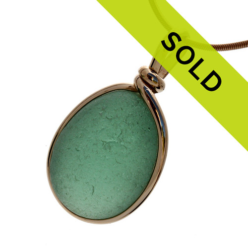 A nice piece of deep seafoam or aqua green with in our signature Original Wire Bezel© pendant setting that leaves both front and back open and the glass unaltered from the way it was found on the beach. SORRY THIS SEA GLASS JEWELRY PIECE HAS BEEN SOLD!