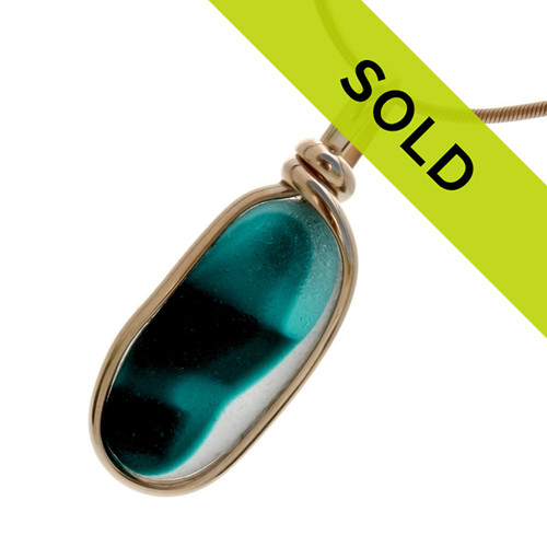 Intense mixed teal or aqua long sea glass piece found on the beaches of Seaham England set in our Original Wire bezel© sea glass pendant setting in 14K Rolled Gold.