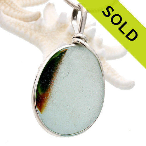 A beautiful mixture of vivid greens and amber fused on a pure white sea glass piece. This piece is set in our Original Wire Bezel© setting and leaves this amazing natural sea glass piece UNALTERED from the way it was found on the beach!