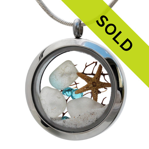 White sea glass and one mixed aquamarine piece combined with a real starfish and seafan in this sea glass locket necklace. Powdery white sand from the West Coast of Florida completes the beachy look! Aquamarine gems make this a great gift for a March Birthday.