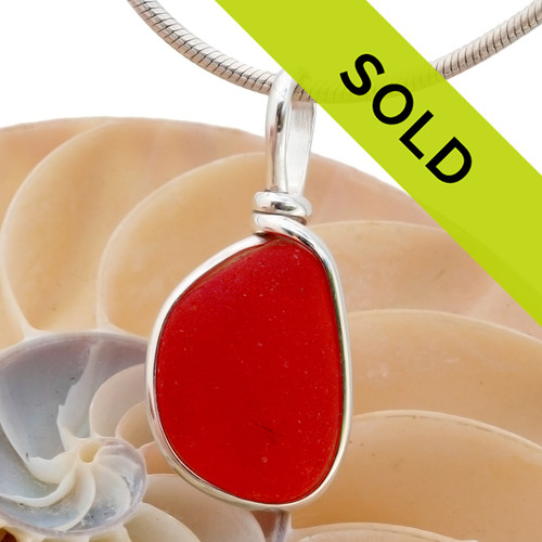 A stunning vivid orange red sea glass piece from England set in our Original Wire Bezel© pendant setting