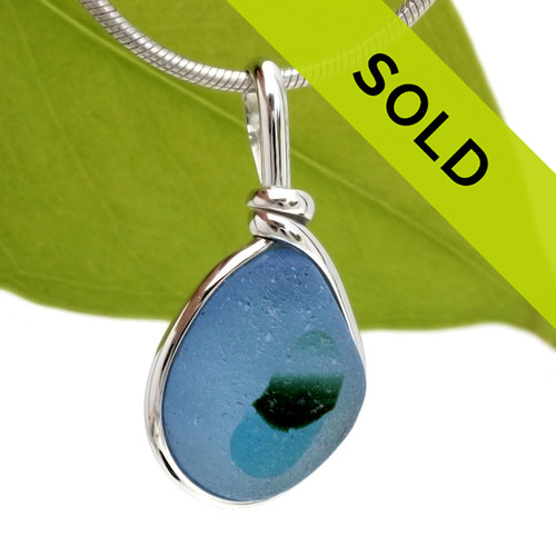 A very bright blue sea glass with spots of aqua and green set in our Original Wire Bezel© pendant setting in sterling silver.  This amazing TOP QUALITY sea glass originates from Seaham England and is the result of years of glass factories discarding their scraps into local waters.  Shown here on our 2mm Snake Chain (Not Included - but recommended and available as an upgrade).