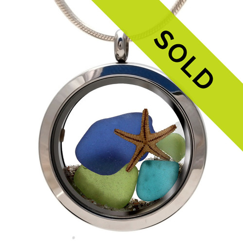 Light and dark blue, vivid lime green and electric rare aqua sea glass pieces make a striking combination in this genuine sea glass locket necklace. A real starfish and  Real beach sand completes your own personal beach on the go!