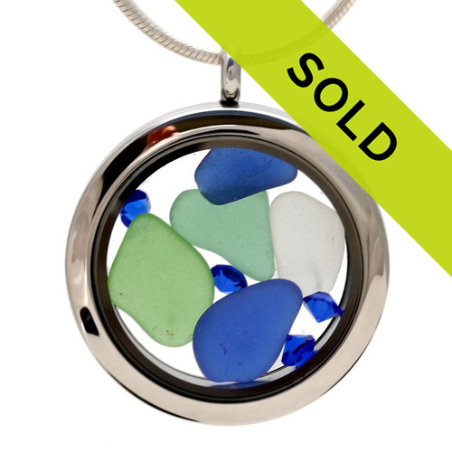 Genuine blue, green and white sea glass pieces make a striking combination in this genuine sea glass locket necklace. Vivid Sapphire blue gems make this color combination pop!