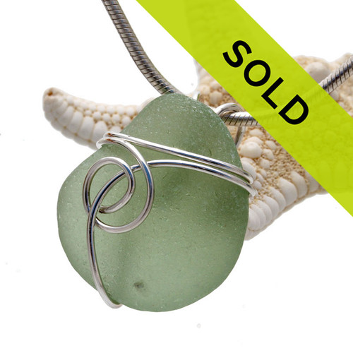 A small piece of olive green sea glass is set in our popular Sea Swirl setting in sterling silver. A nice sea glass pendant for any necklace. This piece does have a small inclusion that is actually a grain of sand stuck in the surface of the sea glass.