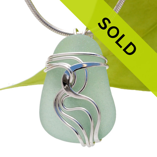 A perfect nicely thick and frosted piece of bright seafoam green sea glass set in our signature Waves©  pendant setting in sterling silver.