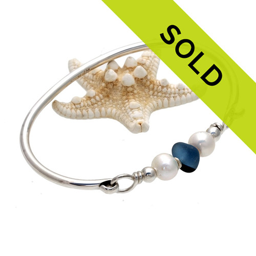 A perfect piece of vivid mixed blue sea glass combined with sterling beads, real fresh water pearls on a sold sterling bangle bracelet. The sea glass is beach found and tumbled only by tide and time found on the beaches of Seaham England.