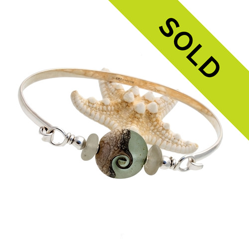 Two white sea glass pieces set with a handmade ocean lovers glass bead set with sterling details on a solid sterling half round bangle bracelet.