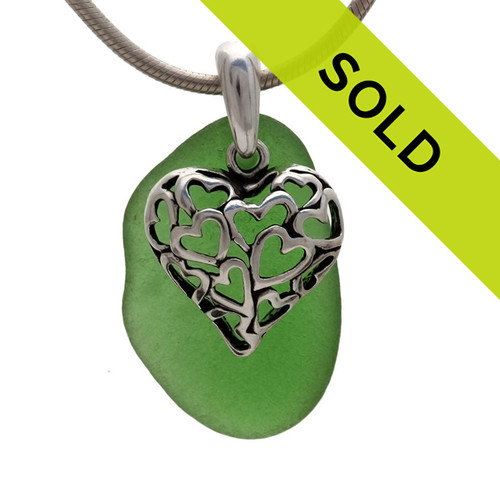 A perfect piece of natural vivid green sea glass set on a solid sterling hand cast bail with a sterling silver heart in hearts charm. A perfect sea glass necklace for any sea glass lover! Sorry this is no longer for sale.