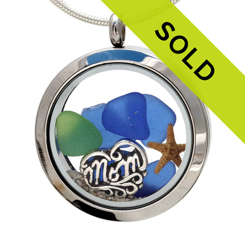 Real sea glass pieces combined with a real starfish and beach sand in this sea glass locket necklace. There is one in every crowd with a single green sea glass piece surrounded in a sea of blue sea glass. A sterling silver heart shaped MOM charm lets her know you are always on her mind, at the beach and always!