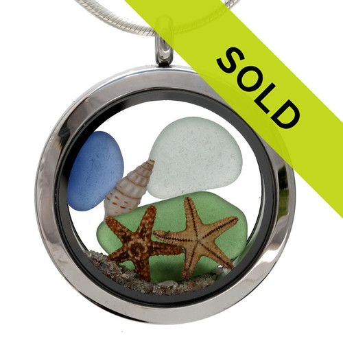 Blue, green and amber genuine beach found sea glass pieces combined in an beachy scene with two starfish  in a stainless steel locket necklace.  Real beach sand completes this beachy look.  This locket is totally customizable by you.