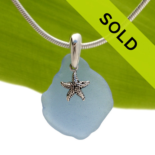 A lovely piece of Carolina or Periwinkle Blue sea glass is combined with a solid sterling starfish and presented on an 18 Inch solid sterling snake necklace chain.