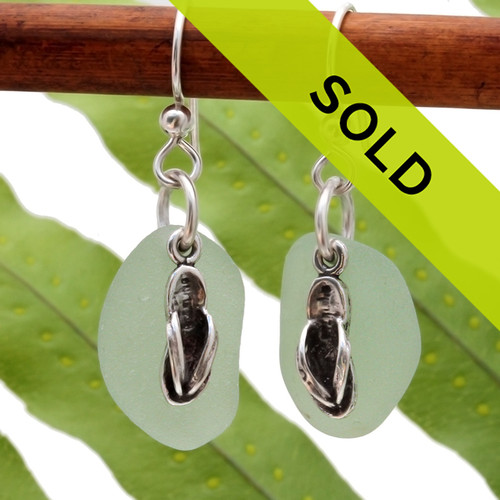 Natural seafoam green sea glass pieces are set with solid sterling flip flop charms and are presented on sterling silver fishhook earrings.