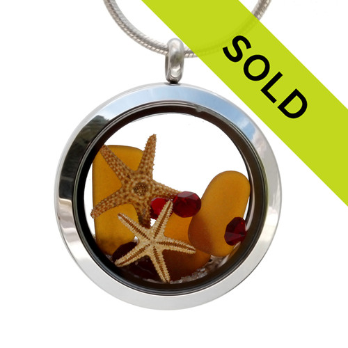 Genuine amber beach found sea glass is combined with crystal ruby gemstones, an two real starfish and beach sand in this silver stainless steel locket necklace.