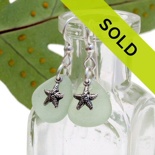 Two perfectly matched pieces of genuine beach found sea glass set with solid sterling starfish charms. Sorry these earrings are no longer for sale.