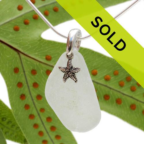 A white piece of TOP QUALITY sea glass set on a solid sterling bail with a sterling sea star charm.
