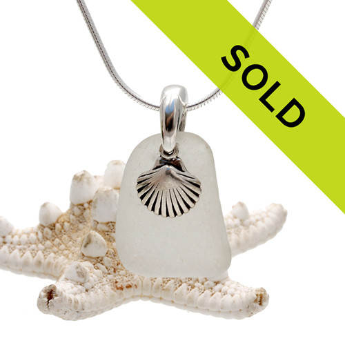 A white piece of TOP QUALITY sea glass set on a solid sterling bail with a sterling sea shell charm. Sorry this piece has sold!