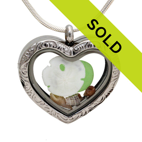 Our new heart lockets make this green sea glass really shine! A tiny sandollar completes the beachy look! Genuine beach found glass. Sorry this sea glass jewelry piece has been sold!