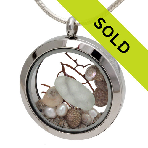 Pale Seafoam Green beach found sea glass piece combined with a real pearls, tiny nautilus shells and a piece of vintage sea fan. Real beach sand completes the beachy look in this sea glass locket necklace. Sorry this locket has sold!