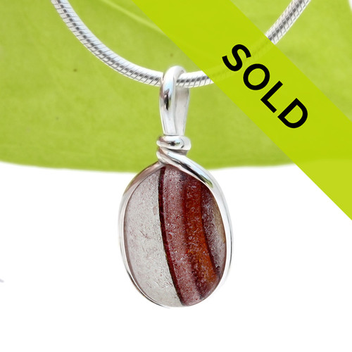 A beautiful mixture of vivid red and gold fused on a pure white sea glass piece. This piece is set in our Original Wire Bezel© setting and leaves this amazing natural sea glass piece UNALTERED from the way it was found on the beach! Sorry this sea glass jewelry has sold!