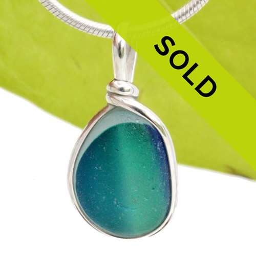 An amazing combination of vivid mixed blue  and aqua green in a light blue base in this very old English Sea Glass piece and set in our Original Wire Bezel© necklace pendant setting