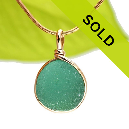 Deep Vivid Aqua Green English sea glass set in our Original Wire Bezel© pendant setting in 14K rolled gold.