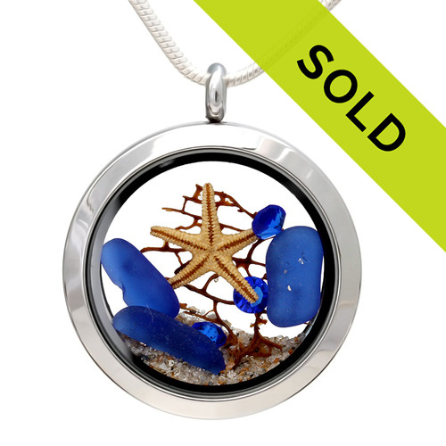 Genuine blue sea glass pieces make a striking combination in this genuine sea glass locket necklace. Vivid Sapphire blue gems make this color combination pop!  Great choice for September Beach Babies! A real starfish and piece of a beach found sea fan complete the beachy look! SORRY THIS LOCKET HAS SOLD