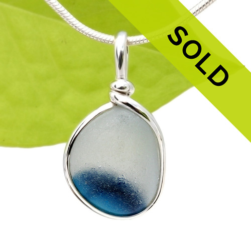 An amazing pure white base encloses a half moon of vivid aqua blue or teal in this Ultra Rare piece of sea glass from England. This piece was once the tip of a punty or pontil rod used to gather and work glass in the kiln. The color being worked was a teal blue at the bottom. Sorry this pendant is no longer for sale.