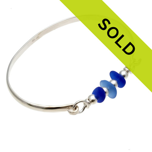 Three pieces of beach found sea glass in light and dark blue on this solid sterling silver half round sea glass bangle bracelet. Sorry this sea glass jewelry piece has been sold!